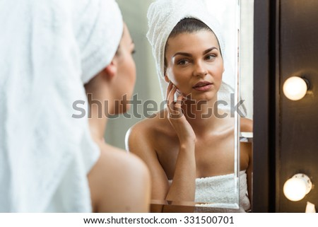 Portrait of a beautiful girl inspecting her skin - stock photo