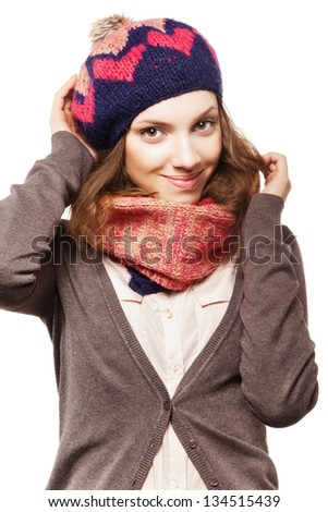 Portrait of a beautiful girl keeping her beret with one hand and hair with another, looking at camera and smiling - stock photo