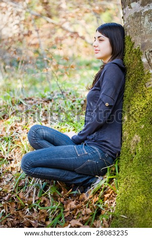 Portrait of a beautiful girl leaning against a tree trunk