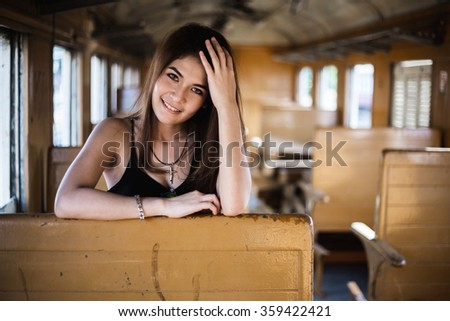 Portrait of a beautiful girl on the bogie of old train - stock photo