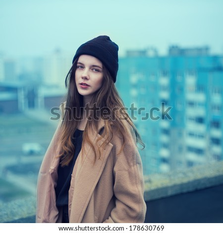portrait of a beautiful girl on the roof of a hipster. on the street cold weather - stock photo