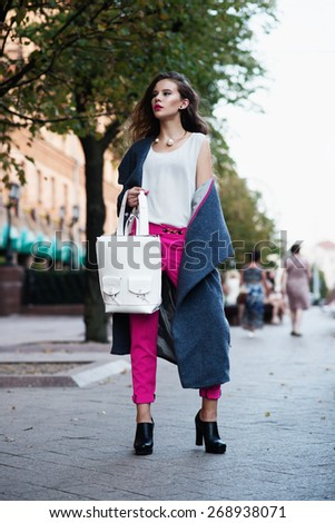 Portrait of a beautiful girl on the street in fashionable clothes - stock photo