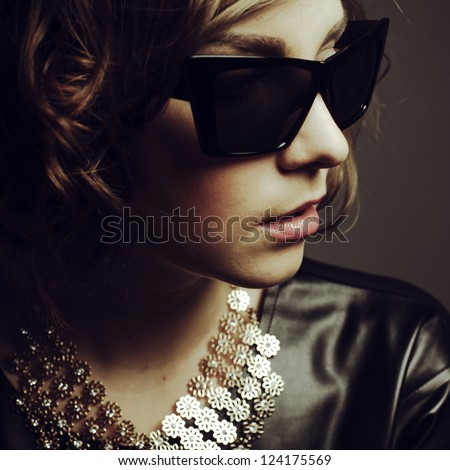 portrait of a beautiful girl posing in studio in leather dress and sunglasses - stock photo