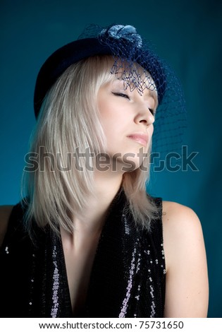 portrait of a beautiful girl's hat with a veil on a blue background - stock photo