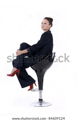 Portrait of a  beautiful girl sits on the bar stool on a white background closeup - stock photo