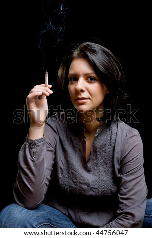 portrait of a beautiful girl smoking a cigar - stock photo