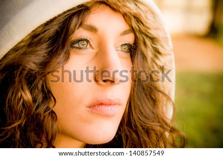Portrait of a beautiful girl wearing a white hood at the park