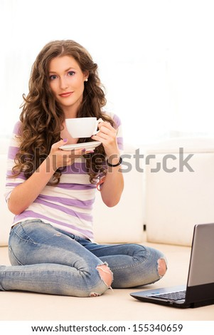 Portrait of a beautiful girl who is sitting on the floor with laptop and drinking coffee