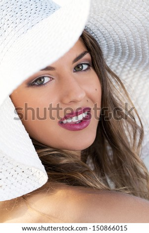 Portrait of a beautiful girl who is wearing a hat and posing near the sea