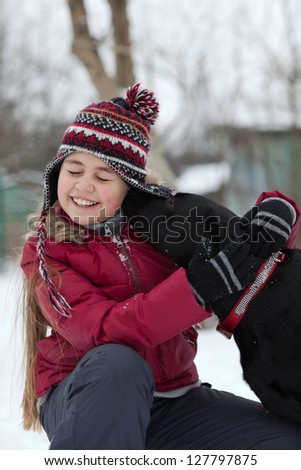 Portrait of a beautiful girl winter outdoors getting a kiss from a black labrador dog. Natural candid moment - stock photo