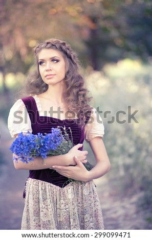 Portrait of a beautiful girl with a big basket of bright blue cornflowers, light, close to the nature of life in a European village in summer, vintage - stock photo
