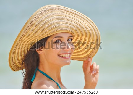Portrait of a beautiful girl with a big hat at the beach, a loving woman is enjoying the sunlight in her swimsuit - stock photo