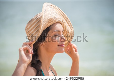 Portrait of a beautiful girl with a big hat at the beach, a loving women is enjoying the sunlight in her swimsuit - stock photo