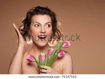 Portrait of a beautiful girl with a bouquet of tulips and wow emotion, closeup. - stock photo