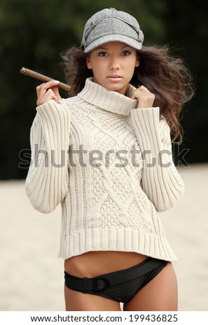 portrait of a beautiful girl with a cigar in the sand - stock photo