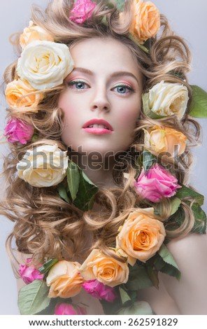 Portrait of a beautiful girl with a gentle pink make-up and lots of flowers in her hair. Spring image. Beauty face. Picture taken in the studio on a gray background. - stock photo
