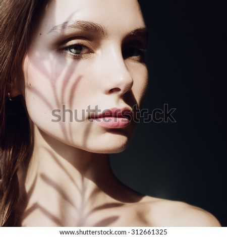 Portrait of a beautiful girl with a shadow on his face - stock photo