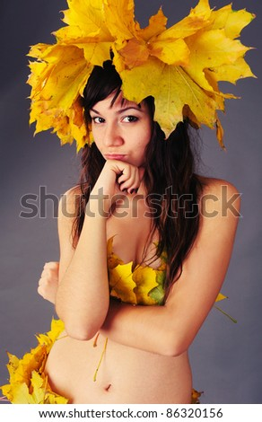 portrait of a beautiful girl with a wreath of autumn leaves on the head