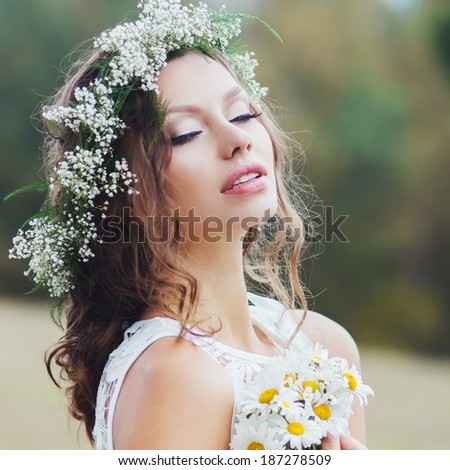 Portrait of a beautiful girl with a wreath of flowers - stock photo