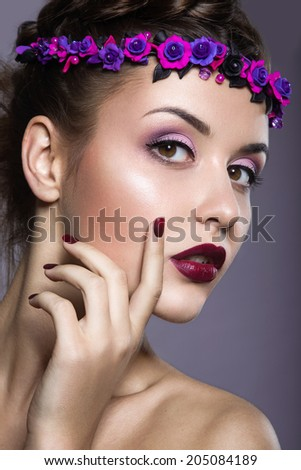 Portrait of a beautiful girl with a wreath of purple flowers on her head. Photo shot in the Studio on a grey background
