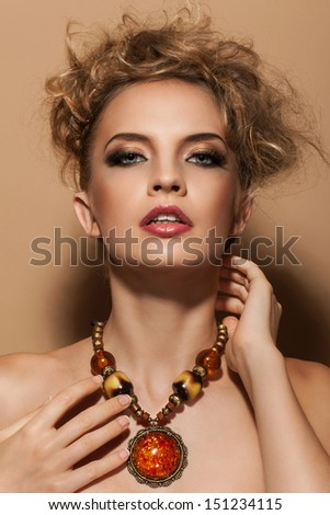 Portrait of a beautiful girl with amber necklace, amazing hairstyle and makeup - stock photo