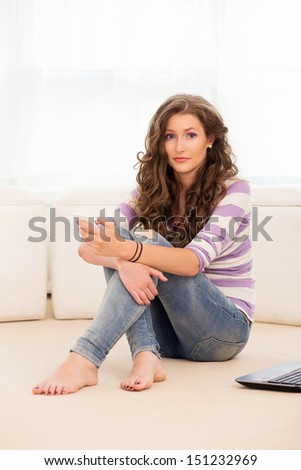Portrait of a beautiful girl with bare feet who is lying on the floor with her laptop