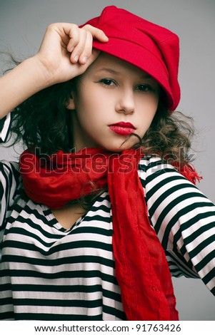 portrait of a beautiful girl with bright makeup, a scarf in a cap and sailor on a dark background - stock photo