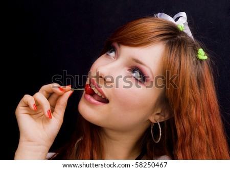 portrait of a beautiful girl with cherries on a black background
