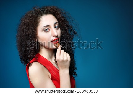 Portrait of a beautiful girl  with curly hair eating chocolate candy heart symbol  - stock photo