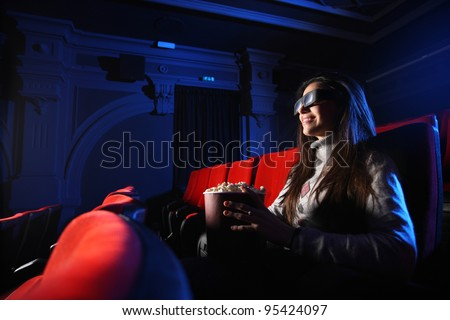 portrait of a beautiful girl with 3D glasses, in a empty movie theater, she eats popcorn and smiles