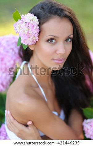 portrait of a beautiful girl with flowers in the summer - stock photo