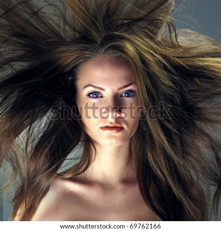 Portrait of a beautiful girl with flying blond hair. Attractive woman with a charmed look - stock photo