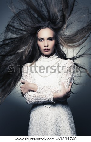 Portrait of a beautiful girl with flying blond hair in white dress - stock photo