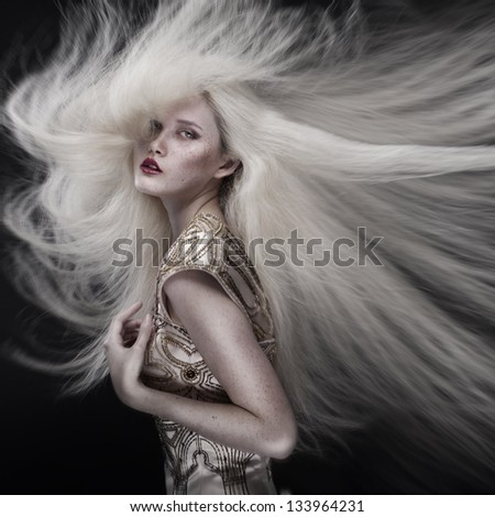 Portrait of a beautiful girl with flying blond hair isolated on black background - stock photo