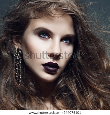 Portrait of a beautiful girl with long curly hair in the studio in the Gothic style, closeup