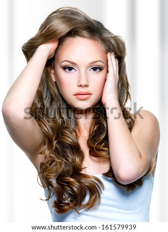 Portrait of a beautiful girl with  long curly hairs - stock photo