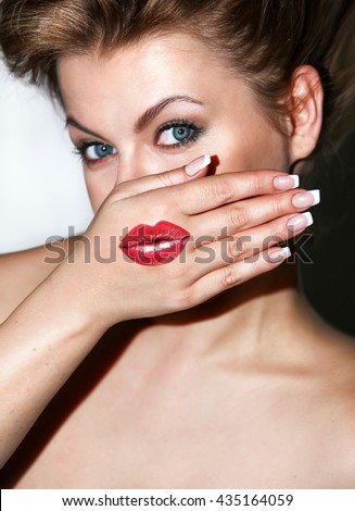 Portrait of a beautiful girl with painted lips on the hand