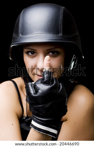 portrait of a beautiful girl with US Army-style motorcycle helmet, and gloves, showing middle finger - stock photo