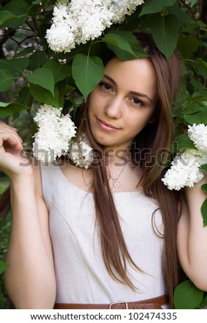 Portrait of a beautiful girl with white lilacs on his head - stock photo