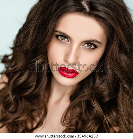 Portrait of a beautiful glamorous brunette with curly hair and bright makeup with red lipstick, close-up, beauty
