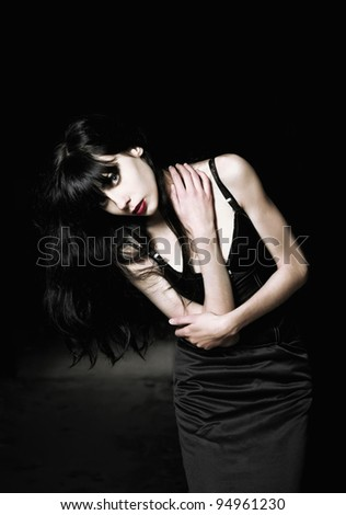 Portrait of a beautiful goth girl among the dark - stock photo