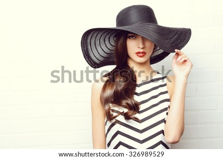 Portrait of a beautiful graceful woman in elegant hat with a wide brim. Beauty, fashion concept. - stock photo