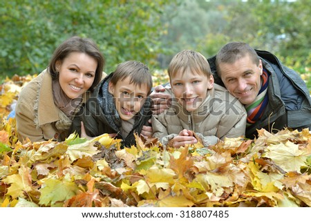Portrait of a beautiful happy family lying in autumn park