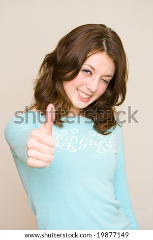 Portrait of a beautiful happy girl in a blue blouse making a thumbs up sign