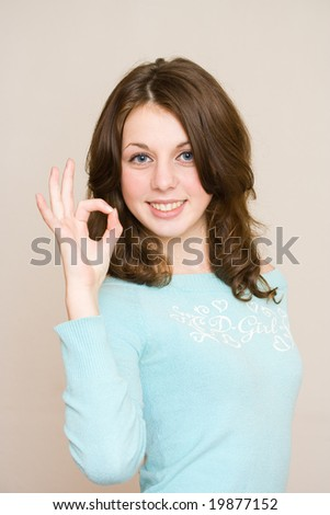 Portrait of a beautiful happy girl in a blue blouse making ok sign