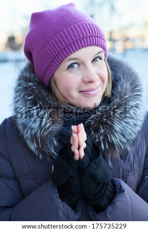 Portrait of a beautiful happy girl in winter clothes looking at the camera - stock photo