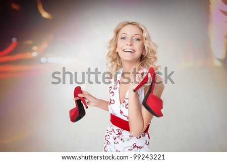 portrait of a beautiful happy girl who holds the red shoes in his hands - stock photo