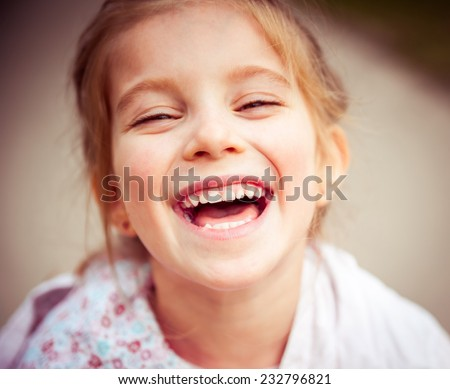 Portrait of a beautiful happy liitle girl close-up - stock photo