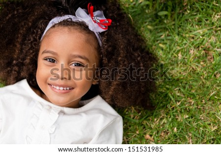 Portrait of a beautiful happy little girl lying outdoors - stock photo