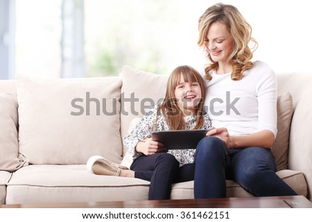 Portrait of a beautiful happy mother and her cute daughter sitting in a beige sofa together and looking digital tablet.